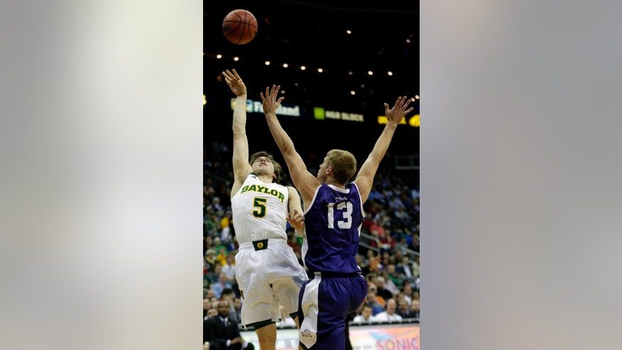Baylor's Brady Heslip (5) shoots under pressure from TCU's Christian Gore (13) during the first half of an NCAA college basketball game in the Big 12 men's tournament on Wednesday, March 12, 2014, in Kansas City, Mo. (AP Photo/Charlie Riedel)