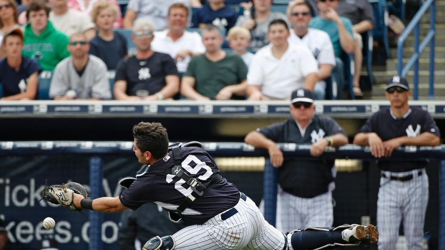 New York Yankees catcher Francisco Cervelli (29) misses a pop fly ball in foul territory during the second inning of a spring exhibition baseball game against the Detroit Tigers in Tampa, Fla., Wednesday, March 12, 2014. New York Yankees manager Joe Girardi watches, far right. (AP Photo/Kathy Willens)