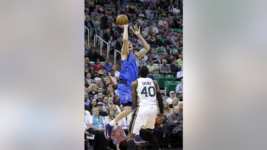 Dallas Mavericks' Dirk Nowitzki, left, shoots as Utah Jazz's Jeremy Evans (40) looks on in the second quarter during an NBA basketball game Wednesday, March 12, 2014, in Salt Lake City. (AP Photo/Rick Bowmer)