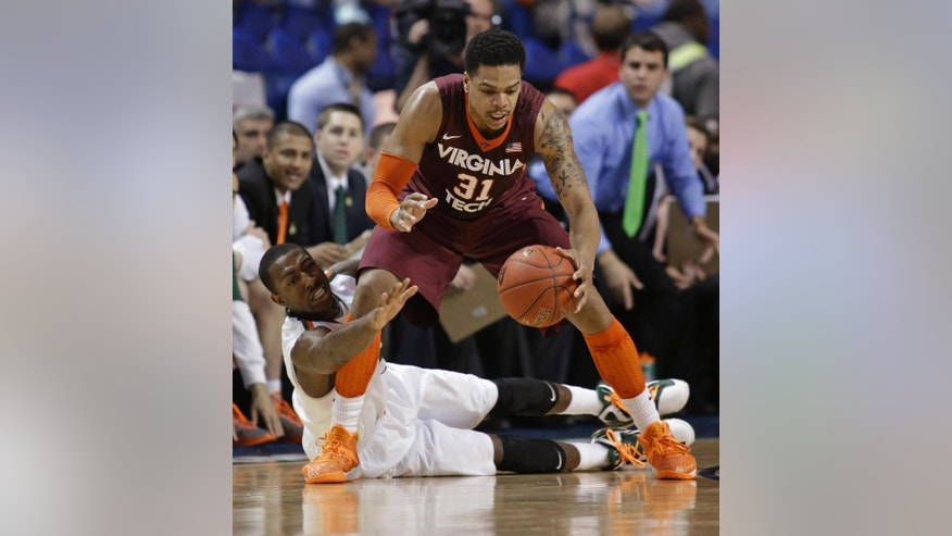 Miami's Davon Reed, bottom, reaches in on Virginia Tech's Jarell Eddie, top, during the first half of a first round NCAA college basketball game at the Atlantic Coast Conference tournament in Greensboro, N.C., Wednesday, March 12, 2014. (AP Photo/Bob Leverone)