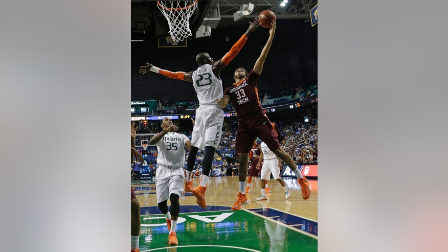Virginia Tech's Marshall Wood (33) shoots over Miami's Tonye Jekiri (23) during the first half of a first-round NCAA college basketball game at the Atlantic Coast Conference tournament in Greensboro, N.C., Wednesday, March 12, 2014. (AP Photo/Gerry Broome)