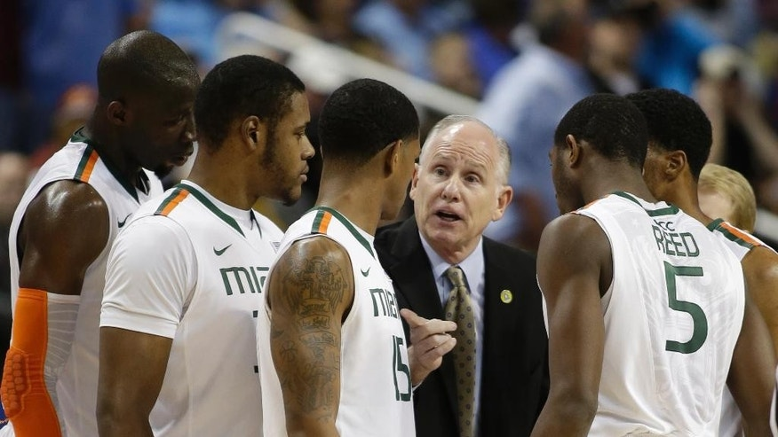 Miami head coach Jim Larranaga, center, talks to his team during a timeout in the first half of a first-round NCAA college basketball game against Virginia Tech at the Atlantic Coast Conference tournament in Greensboro, N.C., Wednesday, March 12, 2014. (AP Photo/Bob Leverone)