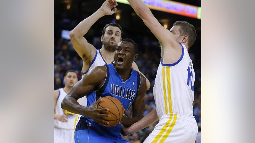 Golden State Warriors' Andrew Bogut, left, and David Lee, right, guard Dallas Mavericks' Samuel Dalembert during the first half of an NBA basketball game Tuesday, March 11, 2014, in Oakland, Calif. (AP Photo/Ben Margot)