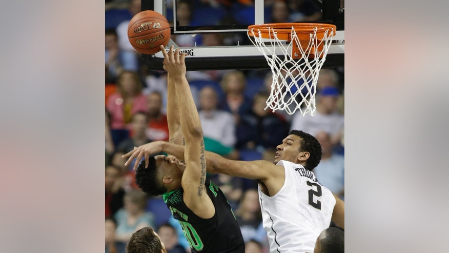 Notre Dame's Zach Auguste (30) is fouled by Wake Forest's Devin Thomas (2) during the second half of a first round NCAA college basketball game at the Atlantic Coast Conference tournament in Greensboro, N.C., Wednesday, March 12, 2014. (AP Photo/Bob Leverone)