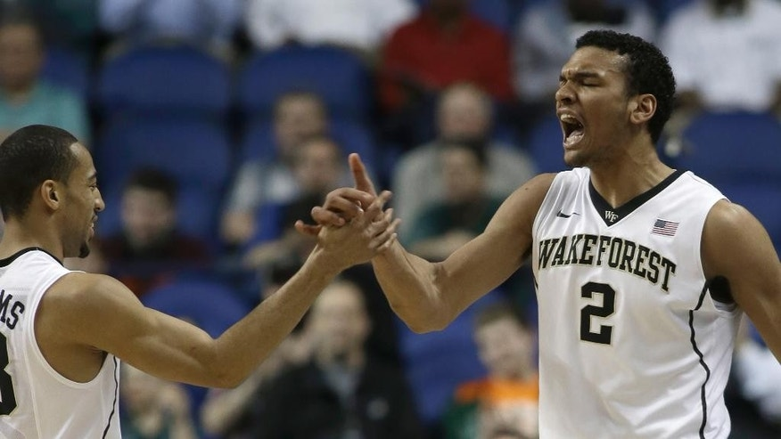 Wake Forest's Devin Thomas, right, reacts with teammate Coron Williams after making a basket against Notre Dame during the first half of a first round NCAA college basketball game at the Atlantic Coast Conference tournament in Greensboro, N.C., Wednesday, March 12, 2014. (AP Photo/Bob Leverone)