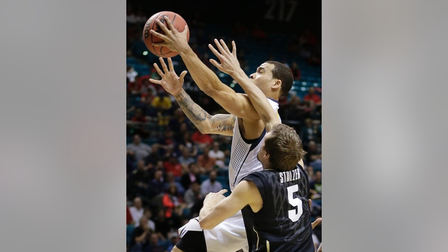 California's Justin Cobbs, left, shoots against Colorado's Eli Stalzer in the first half of an NCAA college basketball game in the Pac-12 men's tournament, Thursday, March 13, 2014, in Las Vegas. (AP Photo/Julie Jacobson)