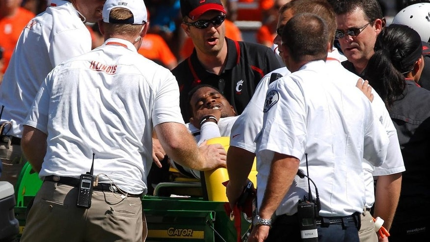 FILE - In this Sept. 7, 2013, file photo, Cincinnati quarterback Munchie Legaux is tended to as he is taken from the field on a cart after being injured during the second half of an NCAA college football game against Illinois in Champaign, Ill. It appeared that Legaux's college career was over last fall when a gruesome knee injury ended his senior season. He's received another year of eligibility from the NCAA and is trying to get healthy enough to compete for his job at Cincinnati this summer. (AP Photo/Andrew A. Nelles, File)