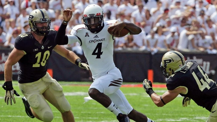 FILE - In this Aug. 31, 2013, file photo, Cincinnati quarterback Munchie Legaux (4) runs the ball against Purdue linebacker Sean Robinson (10) and safety Landon Feichter (44) during the first half of an NCAA college football game in Cincinnati. It appeared that Legaux's college career was over last fall when a gruesome knee injury ended his senior season. He's received another year of eligibility from the NCAA and is trying to get healthy enough to compete for his job at Cincinnati this summer. (AP Photo/Al Behrman, File)