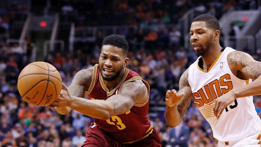 Cleveland Cavaliers' Alonzo Gee, left, loses the ball as it is tipped away by Phoenix Suns' Marcus Morris, right, during the first half of an NBA basketball game on Wednesday, March 12, 2014, in Phoenix. (AP Photo/Ross D. Franklin)