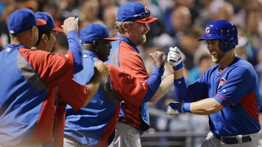 Chicago Cubs' Mike Olt is congratulated after hitting a solo home run during the second inning of a spring exhibition baseball game against the Seattle Mariners Wednesday, March 12, 2014, in Peoria, Ariz. (AP Photo/Darron Cummings)