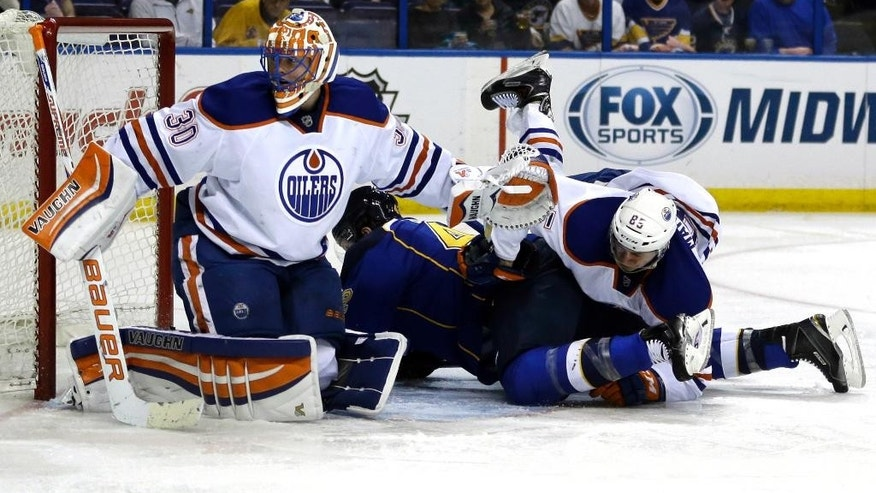 Edmonton Oilers' Martin Marincin, right, of Slovakia, falls over St. Louis Blues' David Backes as Oilers goalie Ben Scrivens, left, looks for the puck during the second period of an NHL hockey game Thursday, March 13, 2014, in St. Louis. (AP Photo/Jeff Roberson)