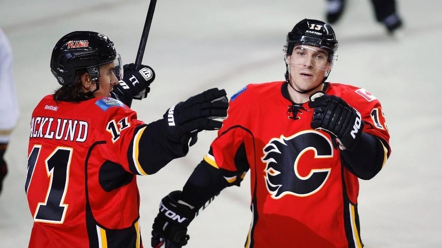Calgary Flames' Mike Cammalleri, right, celebrates his goal with Mikael Backlund, from Sweden, during the first period of an NHL hockey game against the Anaheim Ducks in Calgary, Alberta, Wednesday, March 12, 2014. (AP Photo/The Canadian Press, Jeff McIntosh)