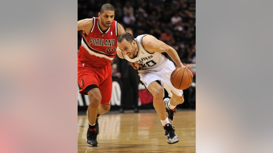 San Antonio Spurs guard Manu Ginobili, right, of Argentina, drives around Portland Trailblazers forward Nicolas Batum during the first half of an NBA basketball game on Wednesday, March 12, 2014, in San Antonio. (AP Photo/Darren Abate)