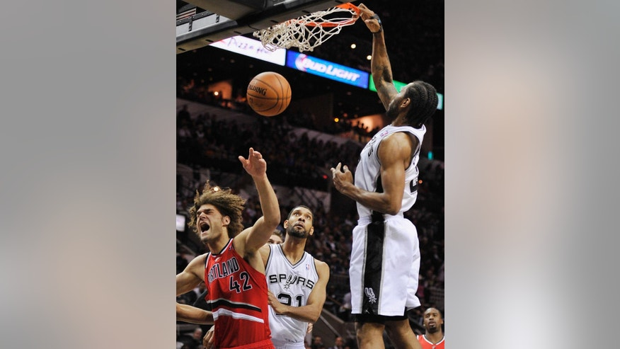 San Antonio Spurs forward Kawhi Leonard, right, dunks over Portland Trailblazers center Robin Lopez, left, as Spurs forward Tim Duncan looks on, during the first half of an NBA basketball game on Wednesday, March 12, 2014, in San Antonio. (AP Photo/Darren Abate)