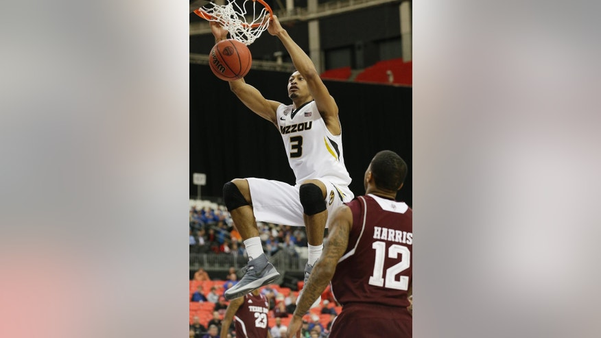 Missouri forward Johnathan Williams, III (3) dunks the ball against Texas A&M guard Fabyon Harris (12) during the second half of an NCAA college basketball game in the second round of the Southeastern Conference men's tournament, Thursday, March 13, 2014, in Atlanta. (AP Photo/Steve Helber)