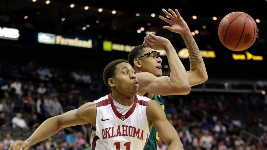 Oklahoma's Isaiah Cousins (11) and Baylor's Isaiah Austin chase a loose ball during the first half of an NCAA college basketball game in the Big 12 men's tournament on Thursday, March 13, 2014, in Kansas City, Mo. (AP Photo/Charlie Riedel)