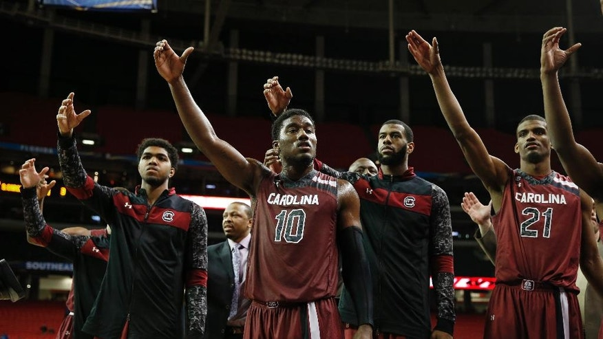 South Carolina guard Duane Notice (10) and other players celebrate after the second half in a first round Southeastern Conference tournament game against Auburn, Wednesday, March 12, 2014, in Atlanta. South Carolina won 74-56. (AP Photo/John Bazemore)