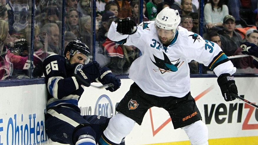 San Jose Sharks' Adam Burish, right, checks Columbus Blue Jackets' Corey Tropp during the second period of an NHL hockey game, Thursday, March 13, 2014, in Columbus, Ohio. (AP Photo/Jay LaPrete)