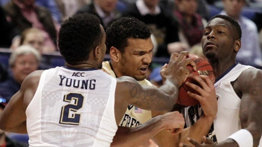 Wake Forest's Devin Thomas, center, is trapped by Pittsburgh's Michael Young, left, and Talib Zanna, right, during the first half of a second round NCAA college basketball game at the Atlantic Coast Conference tournament in Greensboro, N.C., Thursday, March 13, 2014. (AP Photo/Bob Leverone)