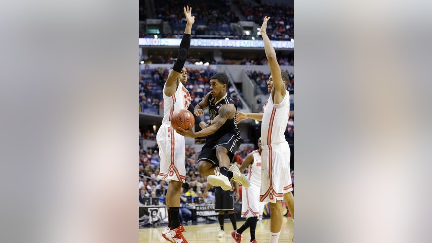Purdue guard Ronnie Johnson tries to pass the ball against Ohio State's Trey McDonald, left, and Marc Loving in the first half of an NCAA college basketball game in the first round of the Big Ten Conference tournament Thursday, March 13, 2014, in Indianapolis. (AP Photo/Michael Conroy)