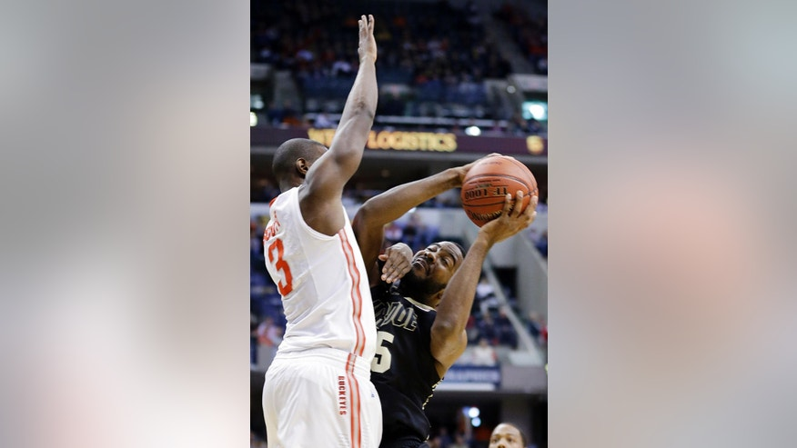 Ohio State guard Shannon Scott (3) tries to block a shot by Purdue guard Rapheal Davis in the first half of an NCAA college basketball game in the first round of the Big Ten Conference tournament Thursday, March 13, 2014, in Indianapolis. (AP Photo/Michael Conroy)