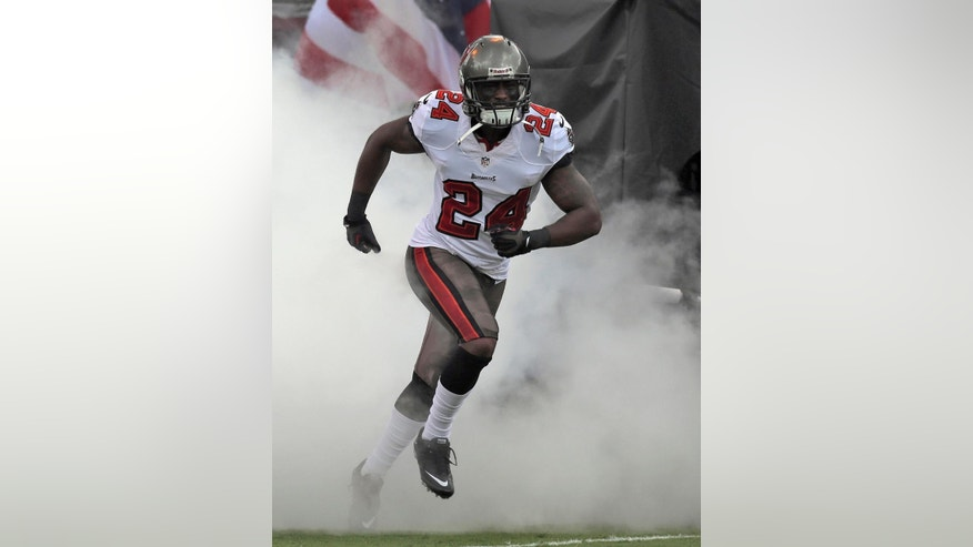 FILE - In this Sept. 15, 2013 file photo, Tampa Bay Buccaneers cornerback Darrelle Revis (24) runs through smoke during team introductions before an NFL football game against the New Orleans Saints, in Tampa, Fla. As Day 2 of the NFL's free-agency period began to unfold, Carolina Panthers receiver Steve Smith and Tampa Bay Buccaneers cornerback Darrelle Revis were waiting to find out whether they might be traded or released. (AP Photo/Chris O'Meara, File)