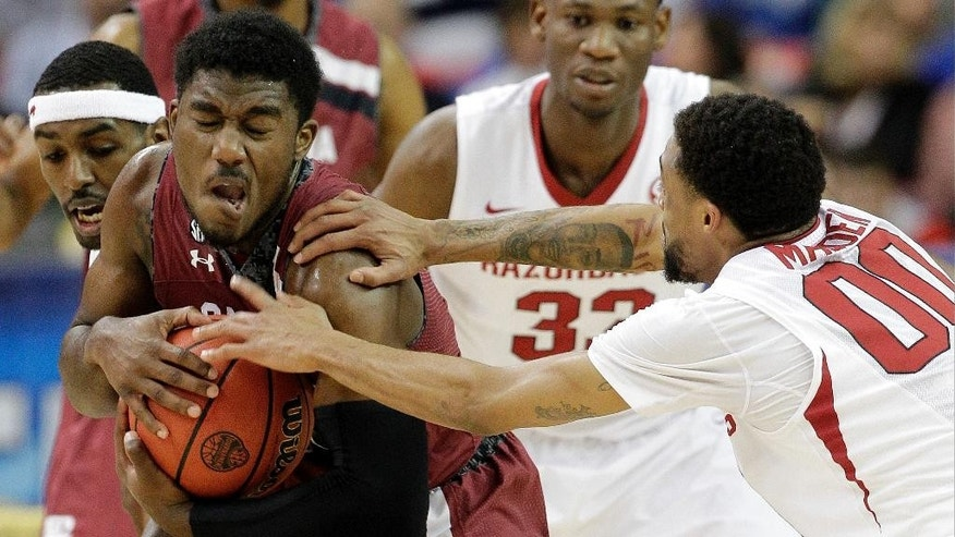 South Carolina guard Duane Notice (10) works to keep the ball as Arkansas' Rashad Madden, Right and Arkansas guard Mardracus Wade (1) defend during the first half of an NCAA college basketball game in the second round of the Southeastern Conference men's tournament, Thursday, March 13, 2014, in Atlanta. (AP Photo/Steve Helber)