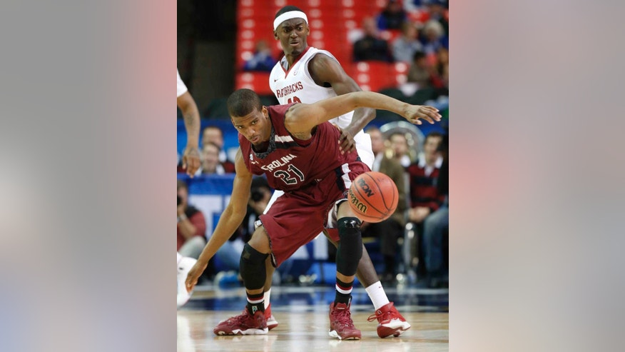 South Carolina's Demetrius Henry (21) prepares to take the ball as Arkansas forward Bobby Portis (10) looks on during the second half of an NCAA college basketball game in the second round of the Southeastern Conference men's tournament, Thursday, March 13, 2014, in Atlanta. (AP Photo/John Bazemore)