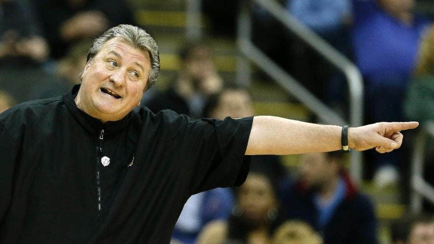 West Virginia coach Bob Huggins motions to his players during the first half of an NCAA college basketball game against Texas in the Big 12 men's tournament on Thursday, March 13, 2014, in Kansas City, Mo. (AP Photo/Charlie Riedel)