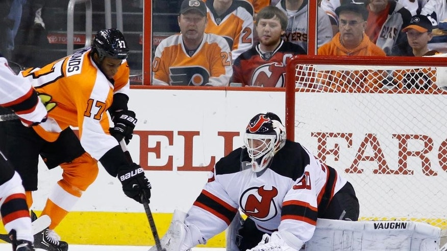 New Jersey Devils' Martin Brodeur, right, blocks a shot by Philadelphia Flyers' Wayne Simmonds during the first period of an NHL hockey game, Tuesday, March 11, 2014, in Philadelphia. (AP Photo/Matt Slocum)