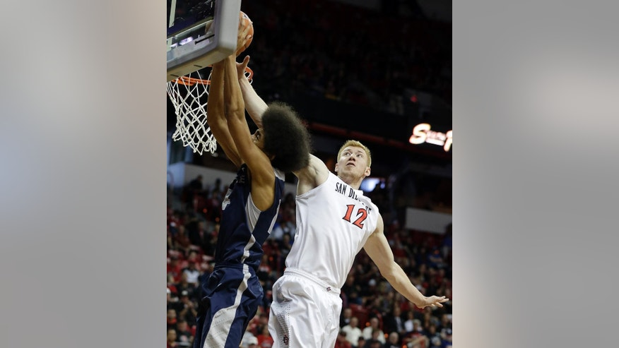 San Diego State's James Johnson (12) covers a shot from Utah State's Jalen Moore during the second half of an NCAA college basketball game in the quarterfinals of the Mountain West Conference tournament on Thursday, March 13, 2014, in Las Vegas. San Diego State defeated Utah State 73-39. (AP Photo/Isaac Brekken)