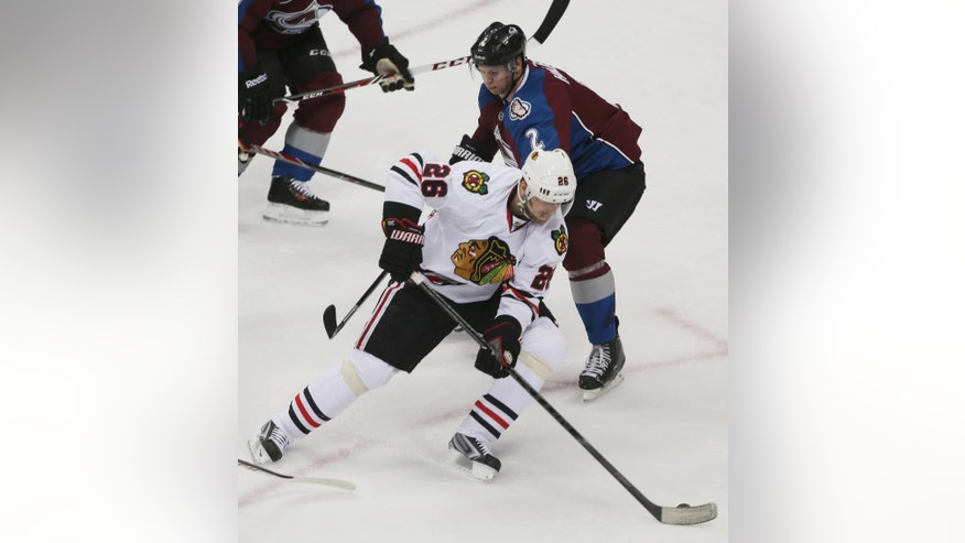 Chicago Blackhawks center Michal Handzus, front, of Slovakia, picks up a loose puck as Colorado Avalanche defenseman Nick Holden covers in the first period of an NHL hockey game in Denver on Wednesday, March 12, 2014. (AP Photo/David Zalubowski)