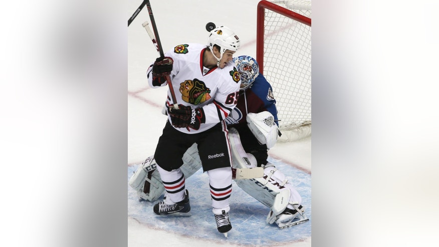 Chicago Blackhawks center Andrew Shaw, front, takes the puck off his helmet while creating a diversion for a shot in front of Colorado Avalanche goalie Semyon Varlamov, of Russia, in the first period of an NHL hockey game in Denver on Wednesday, March 12, 2014. (AP Photo/David Zalubowski)