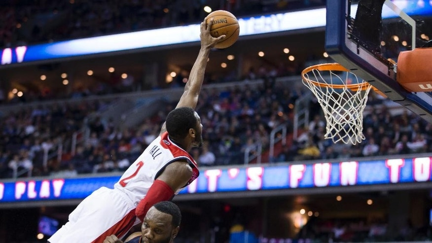 Charlotte Bobcats center Al Jefferson  draws an offensive foul from Washington Wizards guard John Wall during the second half of an NBA basketball game Wednesday, March 12, 2014, in Washington. The Bobcats defeated the Wizards 98-85. (AP Photo/ Evan Vucci)