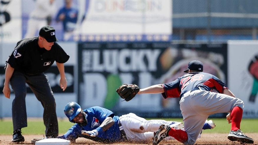 Second base umpire Seth Buckminster (67) watches after Boston Red Sox shortstop Brock Holt (26) tagged Toronto Blue Jays Jose Reyes (7) out trying to stretch a single into a double in the first inning of a spring exhibition baseball game in Dunedin, Fla., Friday, March 14, 2014. The play came when Boston Red Sox right fielder Corey Brown (72) dropped the ball after making a diving catch of Reyes's line drive. (AP Photo/Kathy Willens)