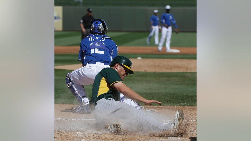 Oakland Athletics' Nate Freiman, foreground, scores as Kansas City Royals' Brett Hayes takes the throw during the second inning of a spring exhibition baseball game on Friday, March 14, 2014, in Surprise, Ariz. (AP Photo/Darron Cummings)