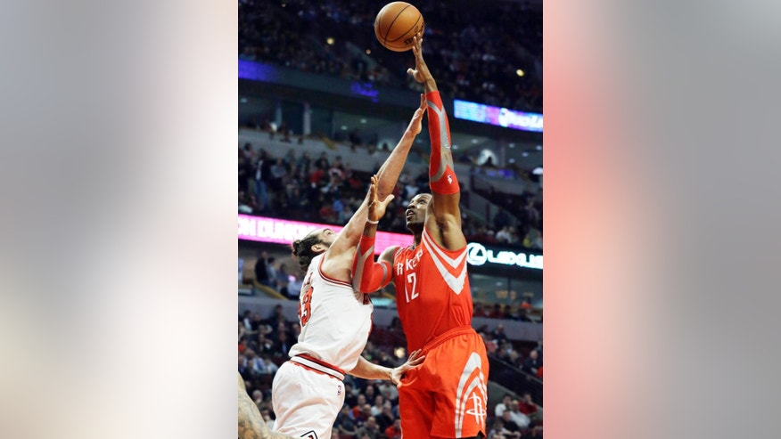 Houston Rockets forward Dwight Howard, right, shoots over Chicago Bulls center Joakim Noah during the first half of an NBA basketball game in Chicago on Thursday, March 13, 2014. (AP Photo/Nam Y. Huh)