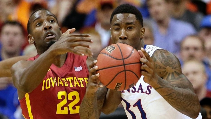 Iowa State's Dustin Hogue (22) and Kansas' Jamari Traylor (31) battle for a rebound during the first half of an NCAA college basketball game in the Big 12 men's tournament on Friday, March 14, 2014, in Kansas City, Mo. (AP Photo/Charlie Riedel)
