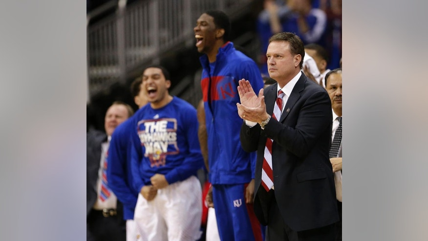 Kansas coach Bill Self, right, and the Kansas bench celebrate a basket during the first half of an NCAA college basketball game against Iowa State in the Big 12 men's tournament on Friday, March 14, 2014, in Kansas City, Mo. (AP Photo/Charlie Riedel)