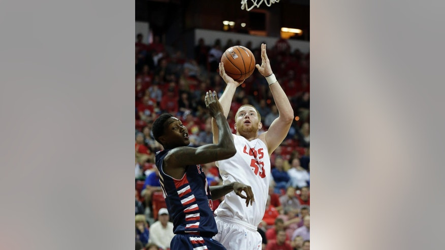 Fresno State's Alex Davis covers a shot from New Mexico's Alex Kirk during the first half of an NCAA college basketball game in the quarterfinals of the Mountain West Conference tournament, Thursday, March 13, 2014, in Las Vegas. (AP Photo/Isaac Brekken)