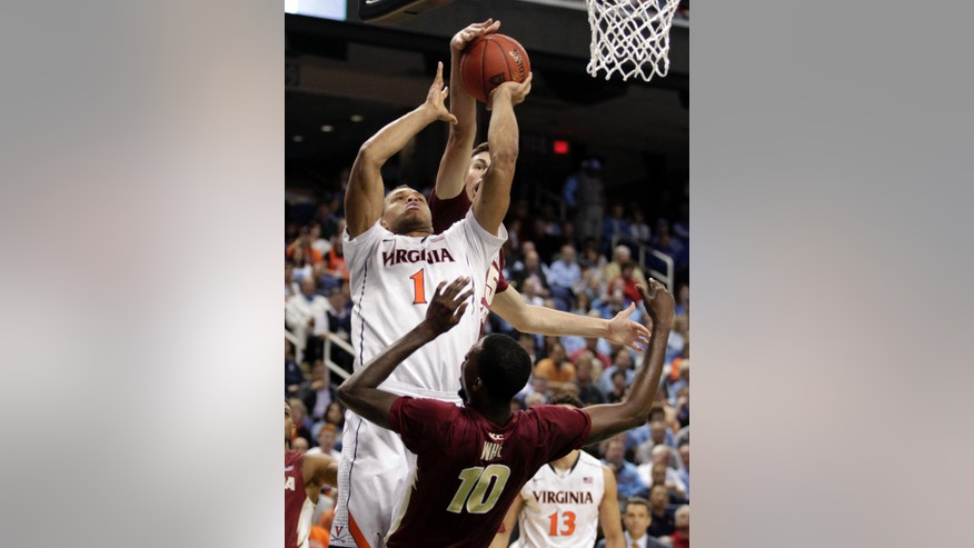 Virginia's Justin Anderson, center, shoots between Florida State's Okaro White, front, and Boris Bojanovsky, back, during the second half of an NCAA college basketball game in the quarterfinal round of the Atlantic Coast Conference tournament in Greensboro, N.C., Friday, March 14, 2014. (AP Photo/Bob Leverone)