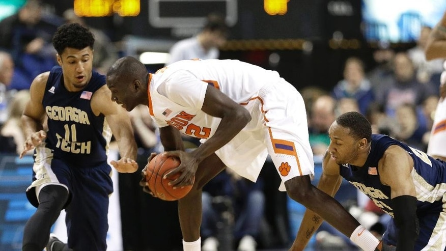 Clemson's Ibrahim Djambo, center, tries to keep the ball from Georgia Tech's Chris Bolden, left, and Kammeon Holsey, right, during the first half of a second round NCAA college basketball game at the Atlantic Coast Conference tournament in Greensboro, N.C., Thursday, March 13, 2014. (AP Photo/Gerry Broome)