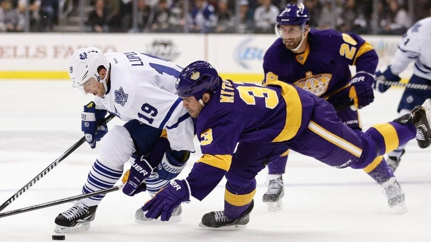 Toronto Maple Leafs' Joffrey Lupul, left, and Los Angeles Kings' Willie Mitchell fight for the puck during the first period of an NHL hockey game on Thursday, March 13, 2014, in Los Angeles.(AP Photo/Jae C. Hong)