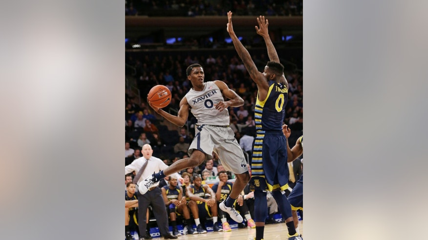 Xavier's Semaj Christon, front left, passes away from Marquette's Jamil Wilson, right, during the first half of an NCAA college basketball game in the quarterfinals of the Big East Conference tournament on Thursday, March 13, 2014, at Madison Square Garden in New York. (AP Photo/Frank Franklin II)