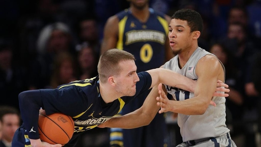 Marquette's Jake Thomas, left, protects the ball from Xavier's Dee Davis (11) during the first half of an NCAA college basketball game in the quarterfinals of the Big East Conference tournament on Thursday, March 13, 2014, at Madison Square Garden in New York. (AP Photo/Frank Franklin II)