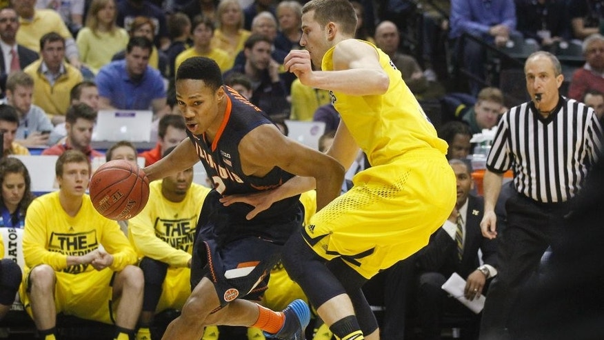 Illinois guard Joseph Bertrand, left, drives the ball against Michigan guard Nik Stauskas in the first half of an NCAA college basketball game in the quarterfinals of the Big Ten Conference tournament Friday, March 14, 2014, in Indianapolis. (AP Photo/Kiichiro Sato)