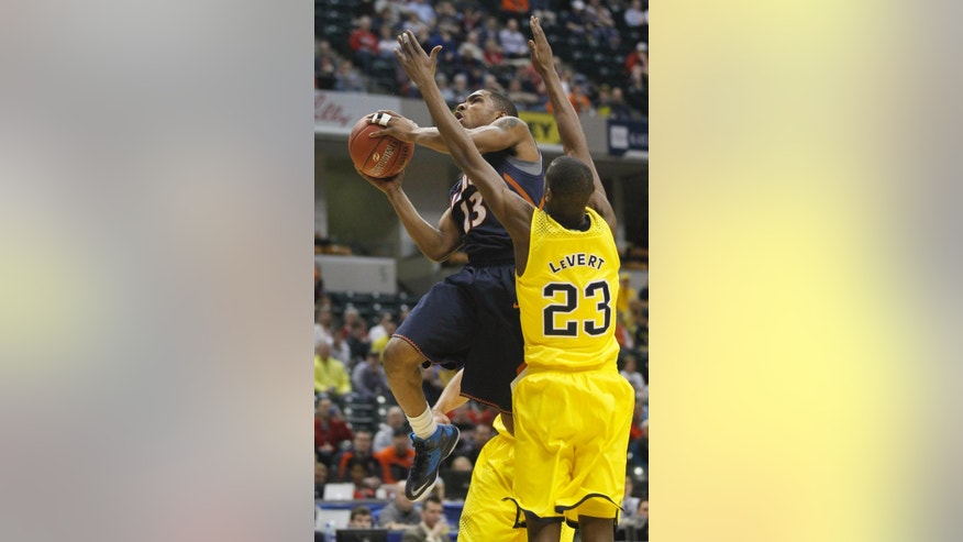 Illinois guard Tracy Abrams (13) goes up for a shot against Michigan guard Caris LeVert (23) in the first half of an NCAA college basketball game in the quarterfinals of the Big Ten Conference tournament Friday, March 14, 2014, in Indianapolis. (AP Photo/Kiichiro Sato)