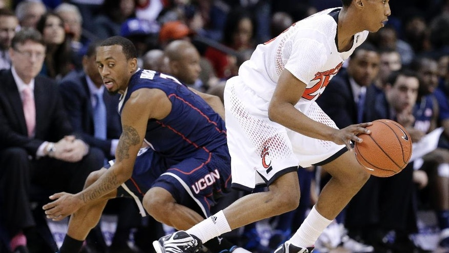 Cincinnati guard Kevin Johnson, right, gets past Connecticut guard Ryan Boatright, left, during the first half of an NCAA college basketball game in the semifinals of the American Athletic Conference tournament Friday, March 14, 2014, in Memphis, Tenn. (AP Photo/Mark Humphrey)