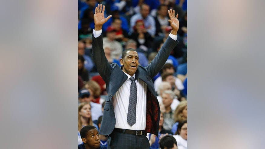 Connecticut coach Kevin Ollie gestures to his players during the first half of an NCAA college basketball game against Memphis in the quarterfinals of the American Athletic Conference men's tournament Thursday, March 13, 2014, in Memphis, Tenn. (AP Photo/Mark Humphrey)
