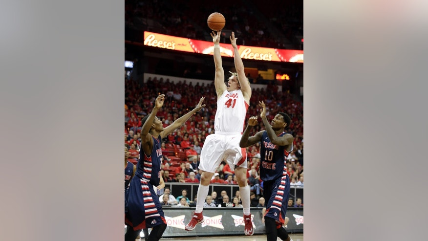 New Mexico's Cameron Bairstow shoots over Fresno State's Paul Watson, left, and Alex Davis during the first half of an NCAA college basketball game in the quarterfinals of the Mountain West Conference tournament ,Thursday, March 13, 2014, in Las Vegas. (AP Photo/Isaac Brekken)